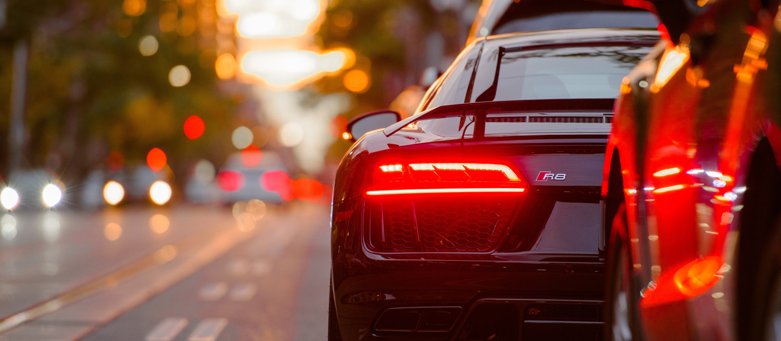 Photo of rear passenger side of black Audi R8, break lights on with blurred background.